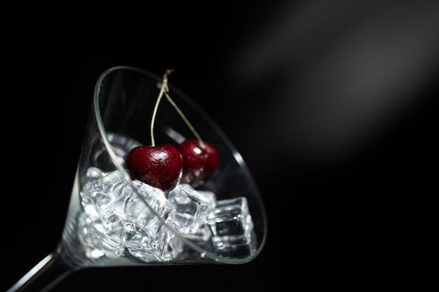 Chiuda sulla vista della ciliegia in un vetro del martini fra ghiaccio nella priorità bassa nera con il chiarore