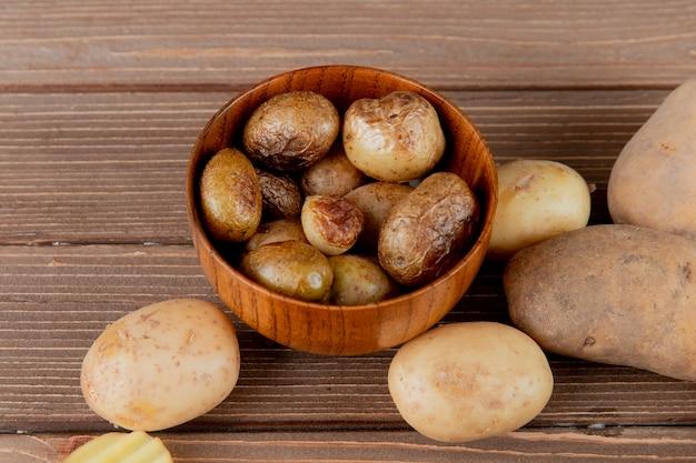 Chiuda sulla vista della ciotola in pieno di patata al forno su fondo di legno con lo spazio della copia