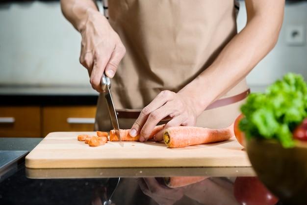 Chiuda sulla vista della mano dell'uomo che affetta la carota sul tagliere
