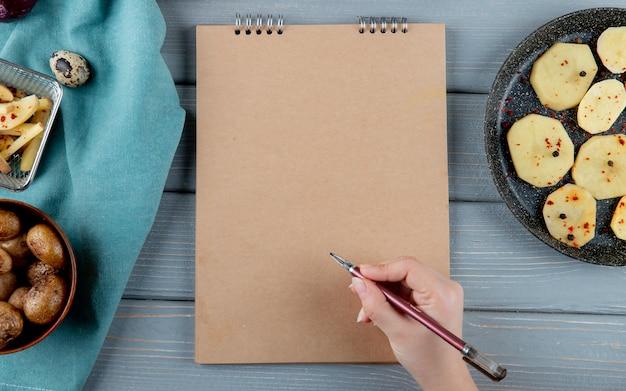 Chiuda sulla vista della penna di tenuta della mano della donna e del blocco note con le patate al forno e affettate intorno su fondo di legno con lo spazio della copia