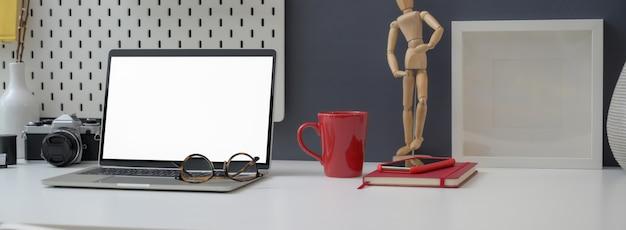 Chiuda sulla vista della scrivania con il computer portatile, le decorazioni e gli articoli per ufficio del modello