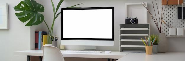 Chiuda sulla vista della stanza minima dell'ufficio con il computer dello schermo in bianco, gli articoli per ufficio e le decorazioni sulla tavola bianca