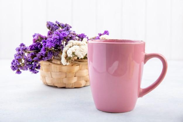 Chiuda sulla vista della tazza di tè con i fiori su superficie bianca