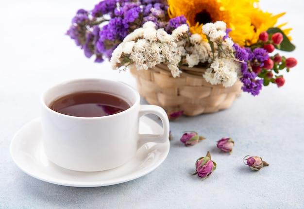 Chiuda sulla vista della tazza di tè sul piattino e sulla merce nel carrello dei fiori e su superficie bianca