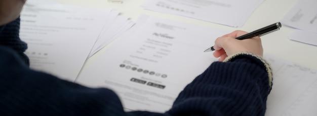 Chiuda sulla vista delle informazioni della lettura della donna di affari sul documento finanziario