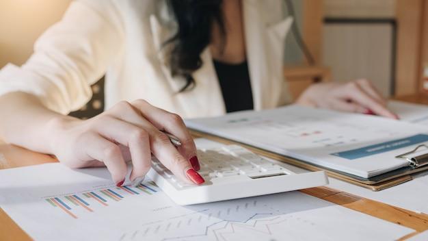 Chiuda sulla vista delle mani dell'ispettore finanziario o del contabile che fanno il rapporto, calcolando o controllando l'equilibrio.