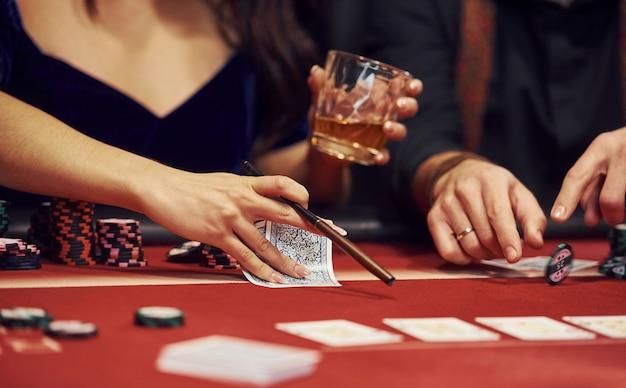 Chiuda sulla vista delle mani eleganti dei giovani che giocano a poker nel casinò