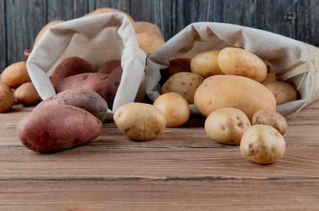Chiuda sulla vista delle patate che si rovesciano dai sacchi su superficie e su fondo di legno con lo spazio della copia