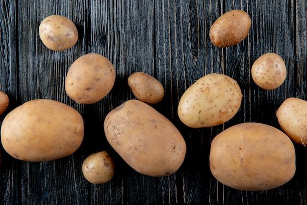 Chiuda sulla vista delle patate su fondo di legno con lo spazio 3 della copia