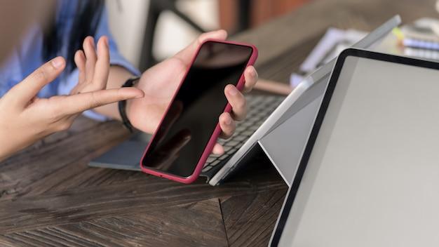 Chiuda sulla vista delle persone di affari che si consultano sul loro progetto con lo smartphone