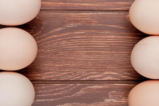Chiuda sulla vista delle uova fresche del pollo su un fondo di legno con lo spazio della copia