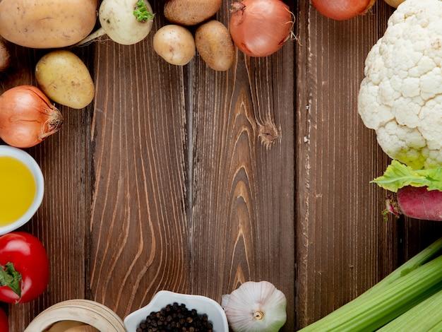 Chiuda sulla vista delle verdure come cavolfiore ed altri dell'aglio della cipolla della patata con burro su fondo di legno con lo spazio della copia