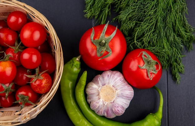 Chiuda sulla vista delle verdure come merce nel carrello dei peperoni, dell'aglio, dell'aneto e del pomodoro e sulla parete nera