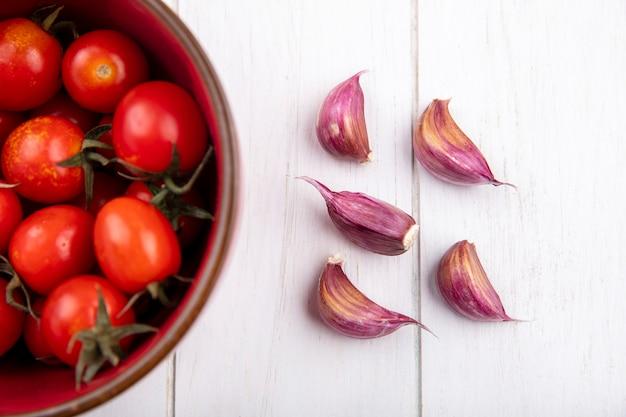 Chiuda sulla vista delle verdure come pomodori in ciotola e spicchi d'aglio sulla parete di legno