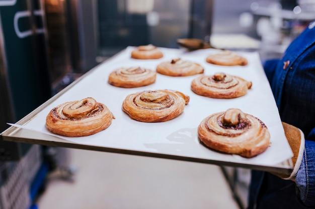 Chiuda sulla vista dello scaffale della tenuta della tenuta della donna di dolci in un forno.
