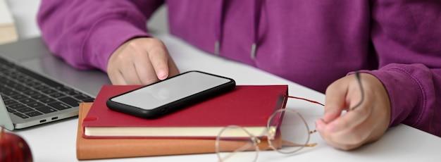Chiuda sulla vista dello studente di college che si rilassa con lo smartphone del modello mentre fa l'assegnazione