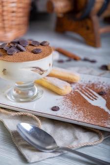 Chiuda sulla vista di bello dessert dolce elegante, tiramisù, servito sul piatto. splendida decorazione, piatto del ristorante, pronto da mangiare. ora del tè, atmosfera accogliente.