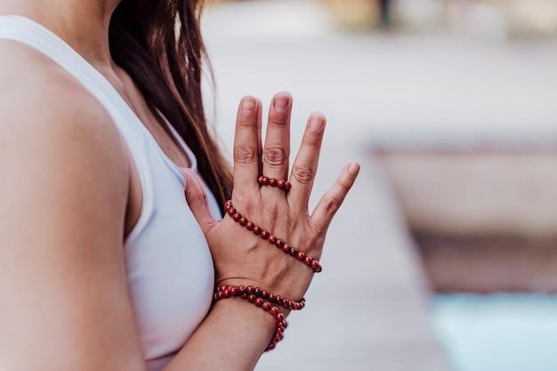 Chiuda sulla vista di giovane donna asiatica irriconoscibile che fa l'yoga in un parco. seduto sul ponte con le mani in preghiera e usando la collana mala. yoga e concetto di stile di vita sano