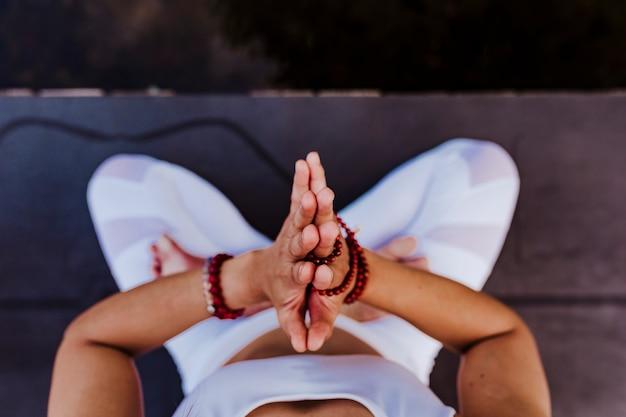 Chiuda sulla vista di giovane donna asiatica irriconoscibile che fa l'yoga in un parco. seduto sul ponte con le mani in preghiera e usando la collana mala.