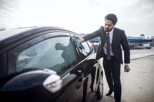 Chiuda sulla vista di giovane uomo laborioso bello barbuto alla moda in vestito che pulisce la sua automobile nera con un panno blu della microfibra sulla stazione manuale di lavaggio dell'automobile di self service.