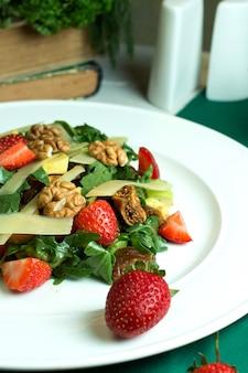 Chiuda sulla vista di insalata fresca con i pomodori ciliegia e le fragole delle noci dell'avocado del parmigiano in una ciotola bianca