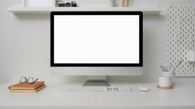 Chiuda sulla vista di l area di lavoro con il computer dello schermo in bianco, gli articoli per ufficio e le decorazioni
