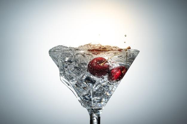 Chiuda sulla vista di spruzzata dell'acqua con la ciliegia di caduta.