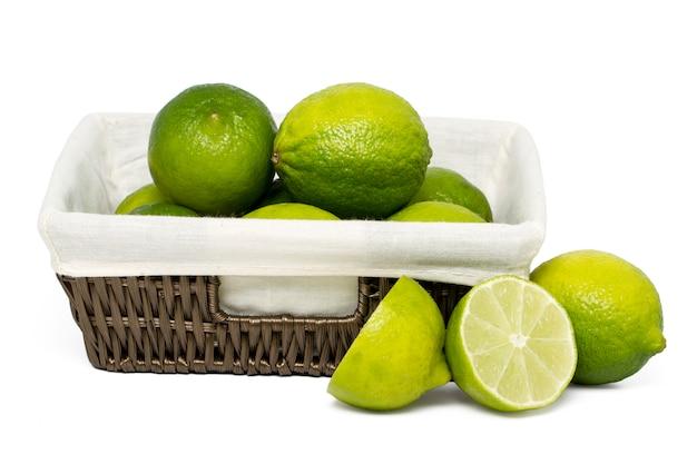 Chiuda sulla vista di un mazzo di frutta della calce all'interno di un cestino di vimini isolato su una priorità bassa bianca.