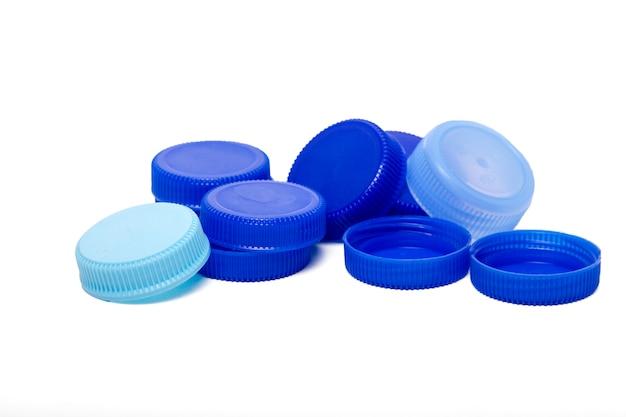 Chiuda sulla vista di un mazzo di protezioni di plastica blu dalle bottiglie dell'acqua isolate su una priorità bassa bianca.