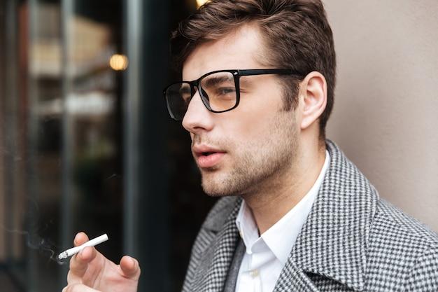 Chiuda sulla vista laterale dell'uomo d'affari serio in occhiali