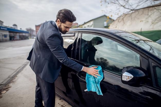 Chiuda sulla vista laterale di giovane tuttofare laborioso barbuto alla moda in vestito che pulisce la sua automobile nera con un panno blu del microfiber sulla stazione manuale di lavaggio dell'automobile di self service.
