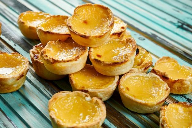 Chiuda sulla vista su gustoso pastel de nata - pasticceria portoghese dell'uovo della crema pasticcera spolverata con cannella sulla tavola di legno. forno.