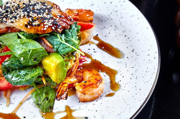 Chiuda sulla vista su insalata calda con gamberetto, avocado, spinaci e salmone sul piatto del wjite. copia spazio per il design. pesce di mare. cibo sano e dietetico. ristorante che serve, pesce alla griglia