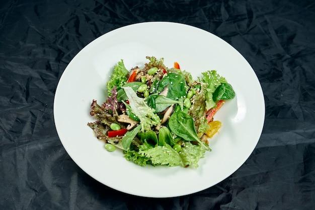 Chiuda sulla vista su insalata con spinaci, funghi, peperone dolce, fagioli e piselli in una ciotola bianca su una tavola nera. alimenti sani e dietetici. vegetariano