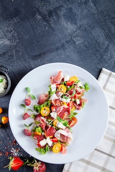 Chiuda sulla vista su insalata fresca e estiva con il pomodoro ciliegia, la fragola, il jamon e il microgreen. piatti gustosi piatti laici. cibo per pranzo sano e delizioso. copia spazio. vista dall'alto