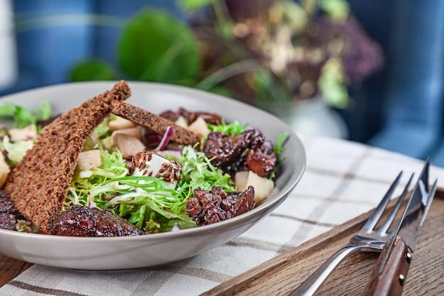 Chiuda sulla vista su insalata sana fresca. insalata con lattuga, fegato di pollo, crostini, cipolle rosse e formaggio