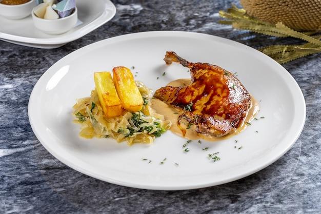 Chiuda sulla vista sul confit della gamba dell'anatra servito con le patate fritte ed il cavolo in salamoia, salsa sul piatto bianco