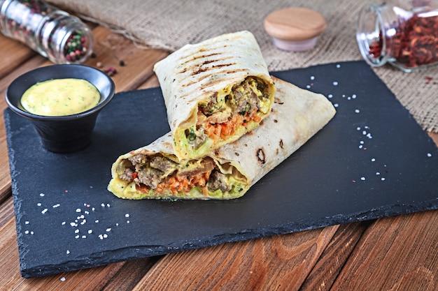 Chiuda sulla vista sul panino di shawarma, giroscopio fresco rotolano in lavash. shaurma è servito su pietra nera. kebab in pita con spazio di copia. spuntino tradizionale mediorientale, fast food. orizzontale da vicino