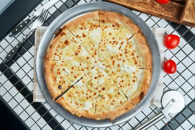 Chiuda sulla vista sulla pizza casalinga saporita dei quattro formaggi italiani in una composizione con le spezie e i pomodori ciliegia su una tavola bianca. vista dall'alto. cibo piatto disteso