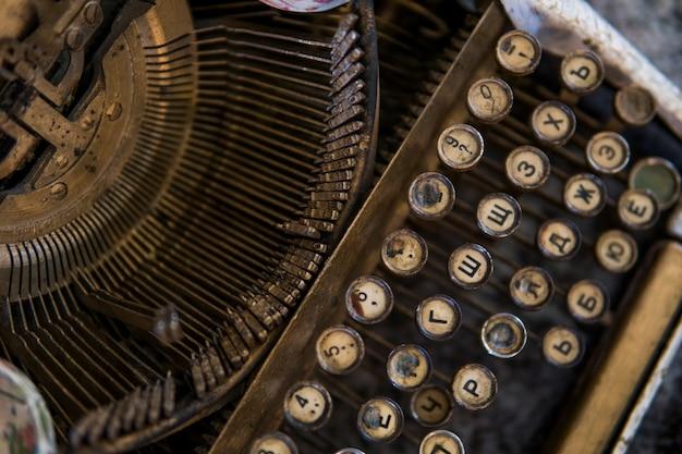 Chiuda sulla vista sulle chiavi di una macchina da scrivere antiche rotte sporche vecchie con le lettere cirilliche di simboli.