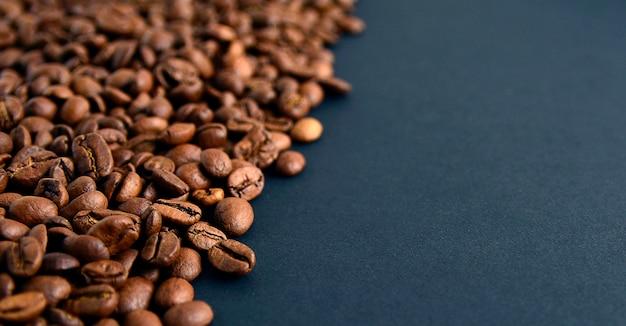 Chiuda sulla vista superiore dei chicchi di caffè arrostiti isolati su fondo nero