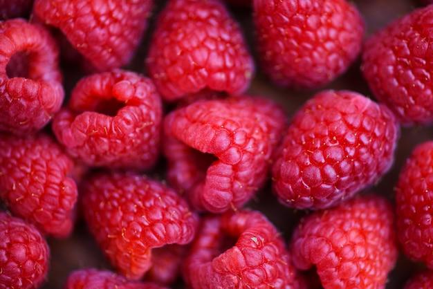 Chiuda sulla vista superiore del fondo rosso della frutta dei lamponi