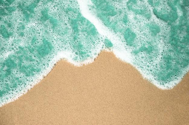 Chiuda sulla vista superiore di acqua piena di bolle sulla spiaggia sabbiosa tropicale