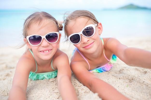 Chiuda sulle bambine sulla spiaggia sabbiosa. bambini felici che si trovano sulla calda spiaggia di sabbia bianca