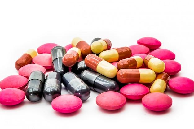 Chiuda sulle capsule di vitamine c e dei supplementi su bianco