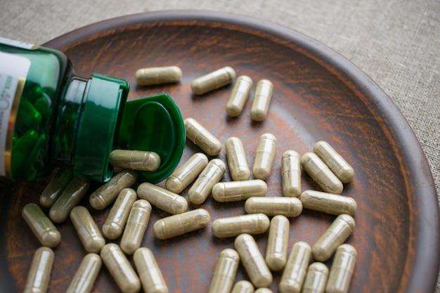 Chiuda sulle capsule e sulla bottiglia di biotina sul piatto di marrone dell'argilla