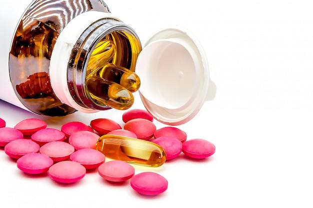 Chiuda sulle capsule e sulla vitamina c dell'olio di pesce con fondo bianco.