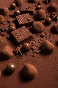 Chiuda sulle cialde e sui tartufi di cioccolato su cacao in polvere