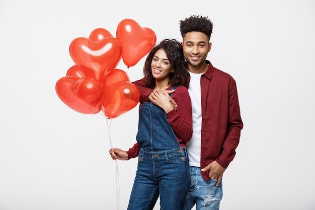 Chiuda sulle coppie afroamericane attraenti che abbracciano e che tengono il pallone rosso del cuore.