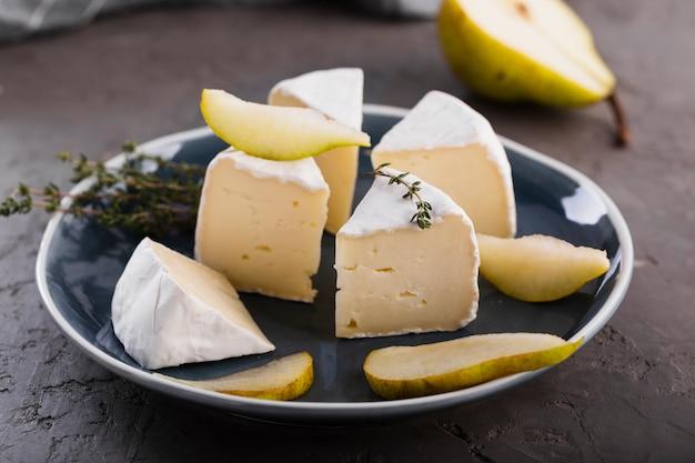 Chiuda sulle fette del camembert con la pera